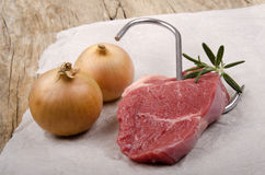 Pork steak on a butchers hook. And onion Royalty Free Stock Image