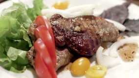 Pork steak with cherry tomatoes and herbs on a white plate stock video