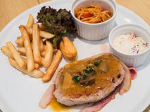 Pork steak with chips and bacon Stock Photo