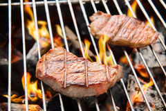 Pork steak cooking over flaming grill. Royalty Free Stock Photo