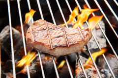 Pork steak cooking over flaming grill. Stock Photos