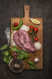 Pork steak on a cutting board with mushrooms and onions mushrooms and garlic tomato lemon and pepper on wooden rustic background t Royalty Free Stock Photography