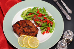 Pork steak dinner. Overhead view of pork steak dinner with sugar snap peas and lemon Royalty Free Stock Photos