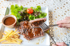 Pork steak. Eating pork steak with salad Royalty Free Stock Images