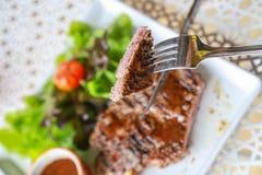 Pork steak. Eating pork steak with salad Royalty Free Stock Photo