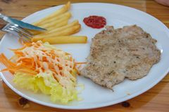 Pork steak with French fries and salad. royalty free stock photo