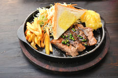 Pork steak with french fries and vegetables Stock Images