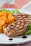 Pork steak fried on grill with mashed sweet potatoes, tasty Stock Image