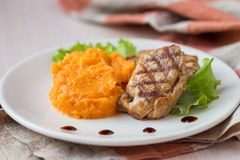 Pork steak fried on grill with mashed sweet potatoes, tasty Royalty Free Stock Photo