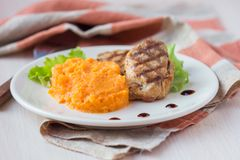 Pork steak fried on grill with mashed sweet potatoes, tasty Royalty Free Stock Photography
