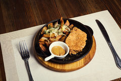 Pork steak with fried potatoes served in a frying pan served wit Royalty Free Stock Photo