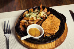 Pork steak with fried potatoes served in a frying pan served wit Stock Images