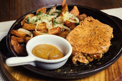 Pork steak with fried potatoes served in a frying pan served wit Royalty Free Stock Photos