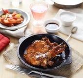 Pork steak in a frying pan, fried vegetables Royalty Free Stock Photo