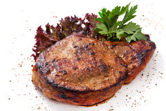 Pork steak with greens, herbs and pepper. On White Background Royalty Free Stock Photo