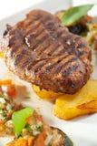 Pork Steak. Grilled Foods - BBQ Pork on Potato with Vegetables Stock Photography