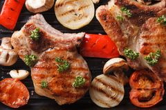 Pork steak grilled with onions and tomatoes. horizontal top view Royalty Free Stock Photo