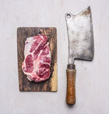 Pork steak for grilling on vintage cutting board with meat cleaver wooden rustic background top view close up Royalty Free Stock Photography