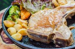 Pork steak. In hot pan Stock Images