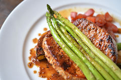 Pork steak. Juicy grill pork steak topped with asparagus Royalty Free Stock Photography