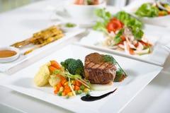 Pork steak. Medium rare pork steak with fresh vegetables Stock Images