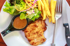 Pork steak moderately cooked with a delicious sauce. French frie. S and fresh salads Royalty Free Stock Photography