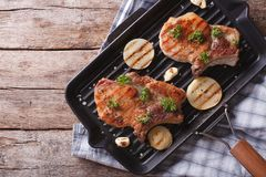 Pork steak with onion in a pan grill, top view horizontal Royalty Free Stock Photography