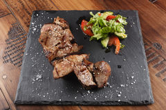 Pork steak pieces. With salad. Wooden background Royalty Free Stock Image