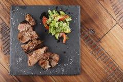 Pork steak pieces. With salad. Wooden background Stock Photos