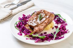 Pork steak with red cabbage and mashed potatoes. On white plate stock photography