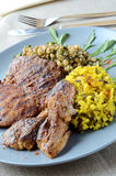 Pork steak with rice and couscous on a blue plate royalty free stock images