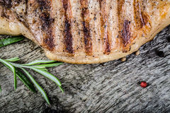Pork steak with rosemary and pepper on old wooden table. Toned Royalty Free Stock Images