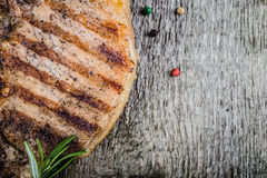 Pork steak with rosemary and pepper on old wooden table. Toned Stock Photography