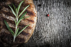 Pork steak with rosemary and pepper on old wooden table. Toned Royalty Free Stock Photos