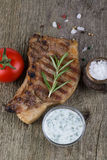 Pork steak with rosemary, tomato and souse on old wooden table Stock Photography