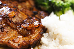 Pork Steak with Salad and Rice. A well fried pork steak (with onions) with garniture of salad and rice - closeup image with a very shallow DOF Royalty Free Stock Image