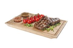 Pork steak with sauces and greens. On whiteboard and white background royalty free stock photos
