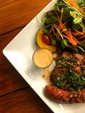 Pork steak and sausage with spicy herbal sauce and salad with dressing in plate pu stock photo