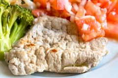 Pork Steak with tomatoes and broccoli, close up Stock Photos