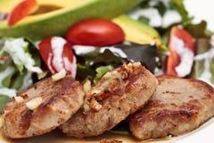 Pork Steak With Vegetables. Closeup of a pork steak with vegetables served on a white plate Stock Image