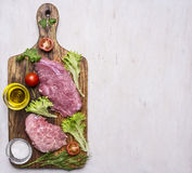 Pork steak with vegetables and herbs, meat knife and fork, on a cutting board  oil and seasonings border ,place for text  on Stock Photos