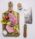 Pork steak with vegetables and herbs, meat knife and fork, on a cutting board  with oil seasonings, and meat cleaver on wooden Royalty Free Stock Photos