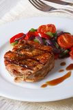 Pork steak with vegetables on a plate close-up, vertical Royalty Free Stock Image