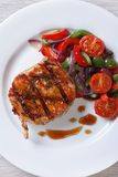 Pork steak with vegetables and sauce top view vertical Royalty Free Stock Image