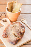 Pork steak on wooden plate Stock Images