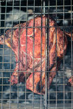 Pork steaks and grill on the burning fire Stock Image