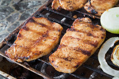 Pork steaks on grill. Close-up image of a pork steaks on grill with garlic, pepper and sliced onion Stock Image