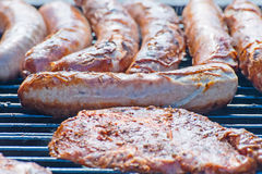 Pork steaks and grilled sausage Stock Photos