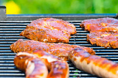 Pork steaks and grilled sausage Royalty Free Stock Image