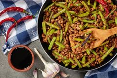 Pork Stir Fry with charred Green Beans. Szechuan Pork Stir Fry with charred Green Beans in a skillet on a concrete table with soy sauce and dried chili peppers Royalty Free Stock Photography